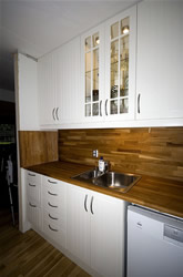 Fitted Kitchen with white cabinets and dark work surface